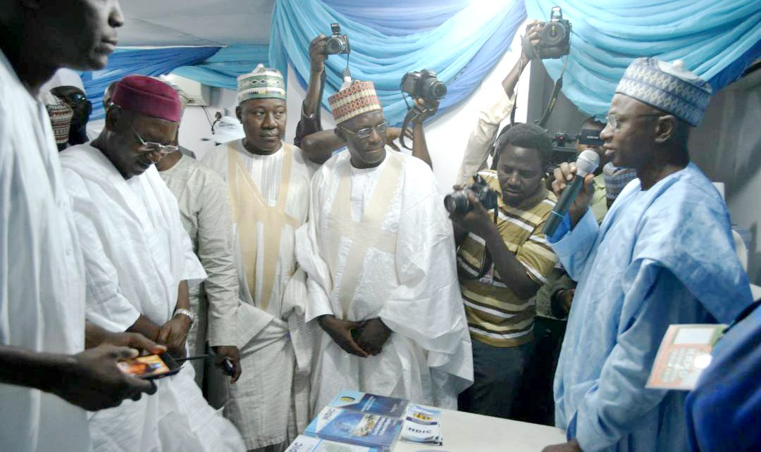 Kano State Deputy Governor, Prof. Hafiz Abubakar (2nd left) and his entourage listen as the Controller, NDIC Kano Zonal Office, Mr. Kabir Oniyangi (1st right) explains the mandate of the NDIC at the 2017 Kano International Trade Fair.