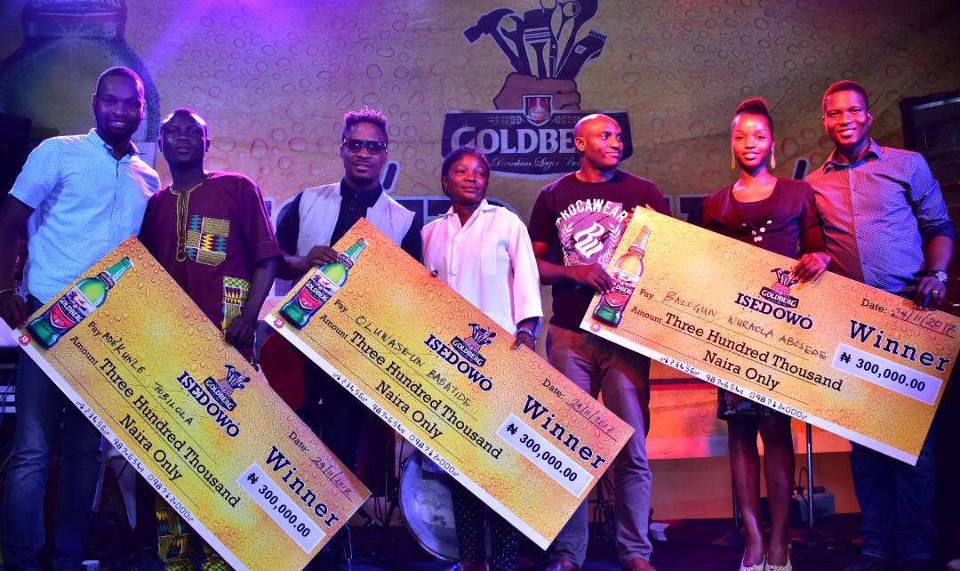 Photo shows Rex Anthony Anieke, Assistant Brand Manager, Regional Mainstream Brands, Nigerian Breweries Plc (1st from Left); Iledare Oluwajuwonlo, popularly known as Jaywon, Guest Performing Artist (3rd from Left); Wilson Umukoro, Area Sales Manager, Ondo, Nigerian Breweries Plc (3rd from Right) and Josiah Akinola, Assistant Brand Manager, Regional Mainstream Brands, Nigerian Breweries Plc (1st from Right). With them are some of the beneficiaries of Goldberg's Isedowo empowerment initiative, during the presentation of business grants to entrepreneurs in Ondo state recently